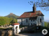 Außenansicht Wallfahrtskirche Maria Zell, im Vordergrund die Friedhofsmauer im Hintergrund die Burg Hohenzollern